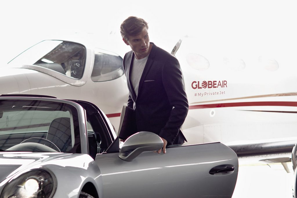 In Auto steigender Geschäftsmann vor einem GlobeAir Privatjet