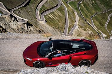 Roter Sportwagen mit Passstraße im Hintergrund